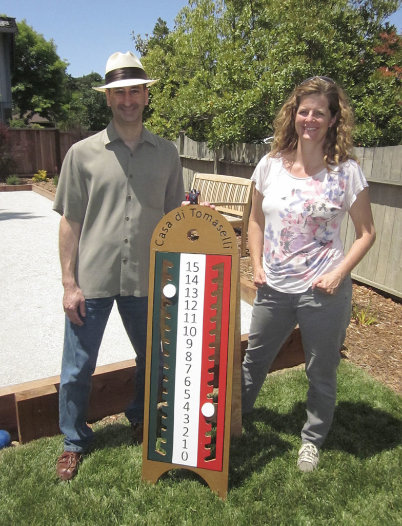 freestanding bocce scoreboard flanked by two people